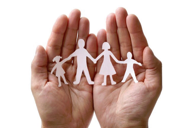 hands holding paper cutout of family holding hands.