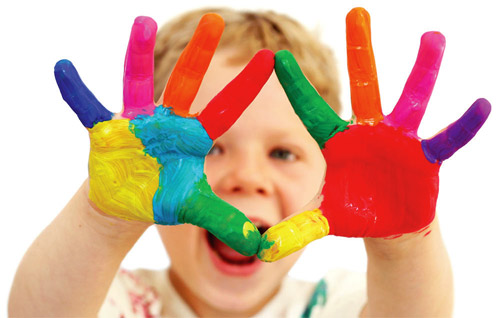 child holding up hands with colourful paint.