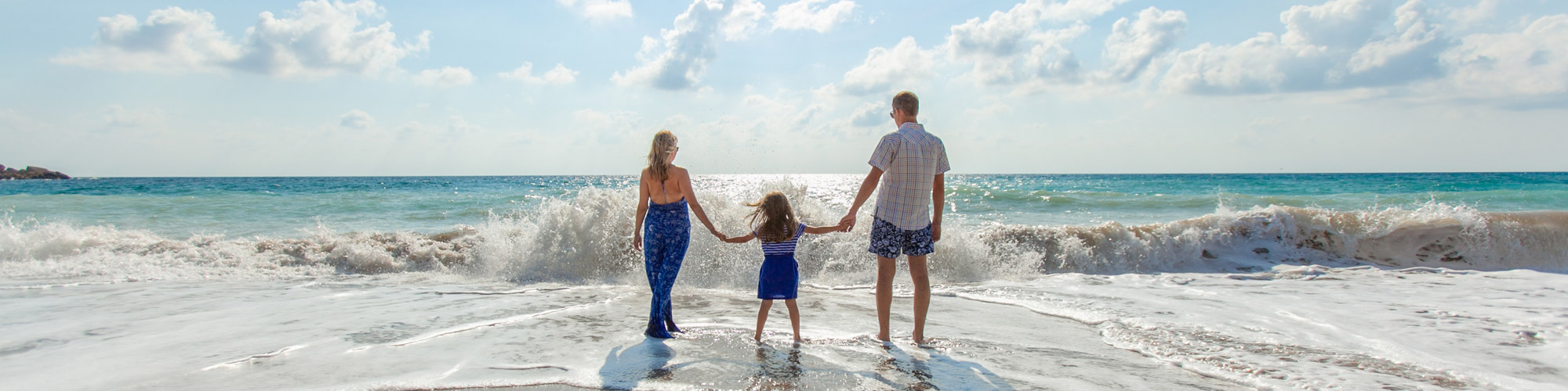 mother and father holding hands with daughter at the beach.